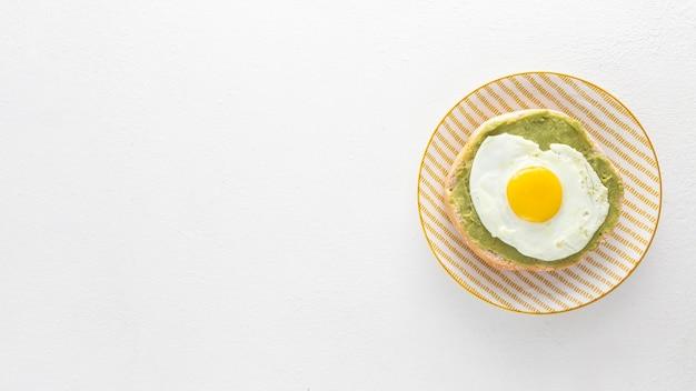 Vista superior da pita com abacate e ovo frito no prato com cópia-espaço