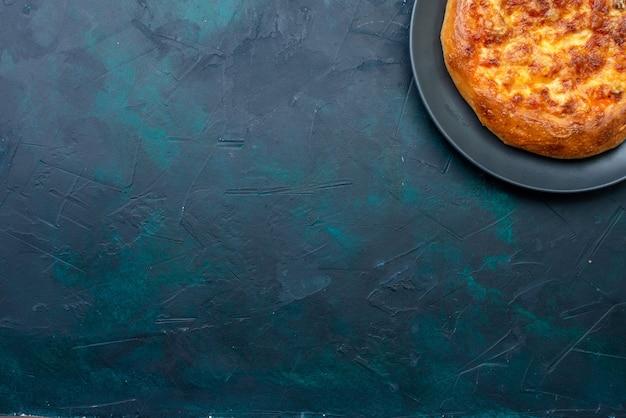 Vista superior da pizza assada recém-saída do forno em uma mesa azul-escura