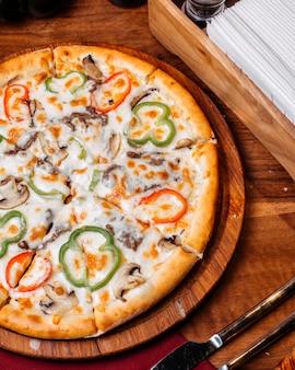 Vista superior da pizza cheia de tomates coloridos pimentões salame e azeitonas em uma placa de madeira