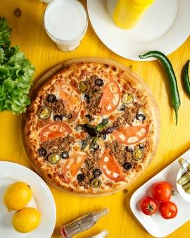 Vista superior da pizza com carne picada, tomate e azeitonas em uma placa de madeira