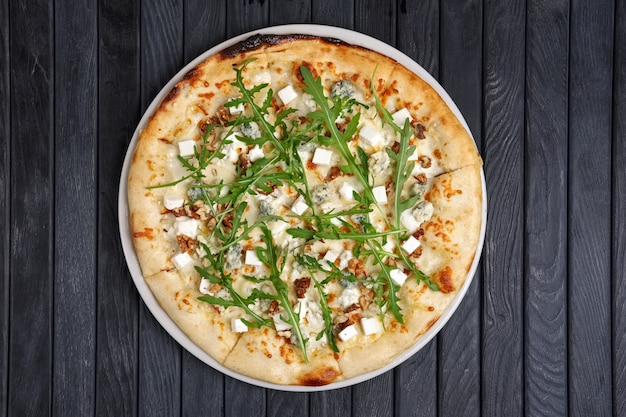 Vista superior da pizza com diferentes tipos de queijo com rúcula