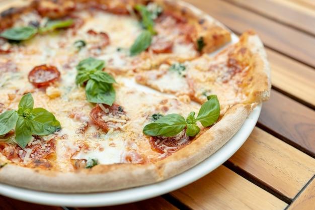 Vista superior da pizza com manjericão na mesa de madeira