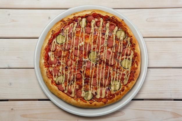 Vista superior da pizza com salsicha e pepino em conserva