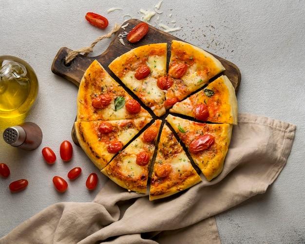 Vista superior da pizza cortada em fatias com tomate e óleo