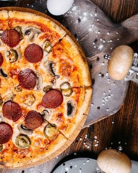 Vista superior da pizza de calabresa com cogumelos e pimentas em uma placa de madeira