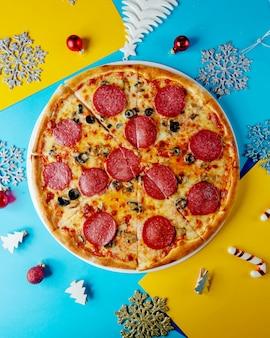 Vista superior da pizza de calabresa com queijo azeitona e cogumelos