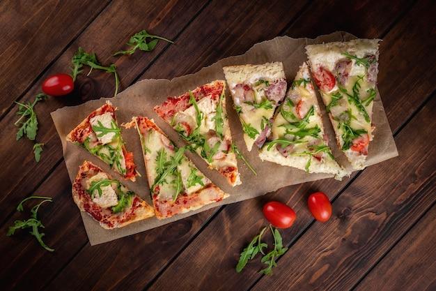 Vista superior da pizza de pão caseiro em fundo de madeira. muitas fatias com tomate cereja, salsicha, salame, bacon, rúcula