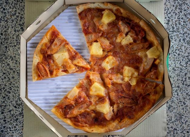 Vista superior da pizza fina e crocante em uma caixa de papelão de entrega
