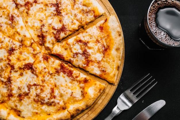 Vista superior da pizza margherita fatiada, servida na bandeja de bambu com bebida