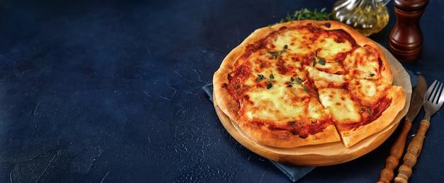 Vista superior da pizza vegetariana deliciosa e crocante margherita em fundo azul escuro