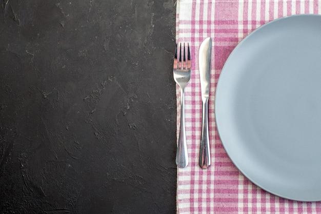 Vista superior da placa azul com garfo e faca na superfície escura