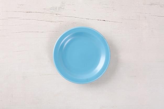 Vista superior da placa azul vazia colocada na mesa de madeira branca com espaço para cópia.