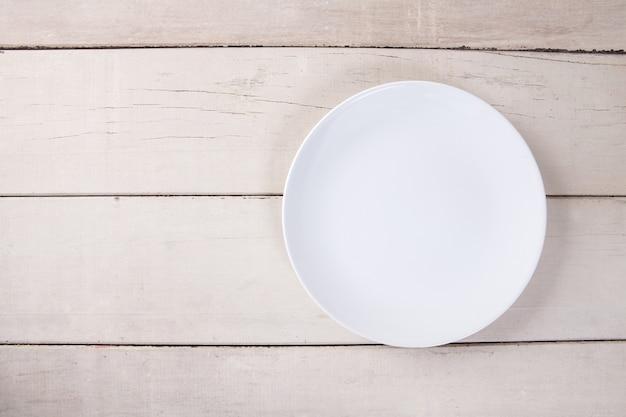 Vista superior da placa branca vazia colocada na mesa de madeira branca com espaço para cópia.