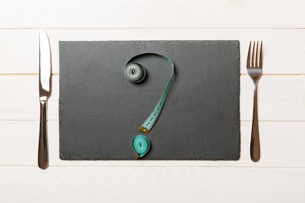 Vista superior da placa de ardósia, garfo e fita métrica em forma de ponto de interrogação em madeira. comer demais e copyspace