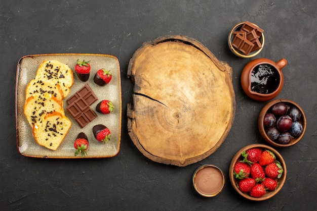 Vista superior da placa de corte de bolo e morangos entre pedaços de bolo com chocolate à esquerda e tigelas com morangos e frutas vermelhas e calda de chocolate no lado direito da mesa