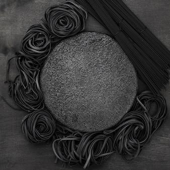 Vista superior da placa de pedra com espaguete preto e tagliatelle
