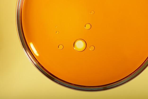 Vista superior da placa de petri com óleo cosmético dentro. fundo amarelo com espaço de cópia, fotografia macro.