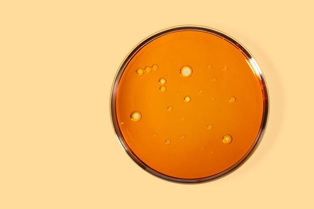 Vista superior da placa de petri com óleo cosmético dentro. fundo amarelo com espaço de cópia.