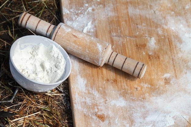 Vista superior da placa de trabalho com farinha e rolo ao lado de uma tigela de farinha que se encontra na grama, o conceito de cozinhar na natureza