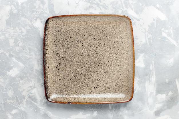 Vista superior da placa quadrada vazia e marrom na superfície branca