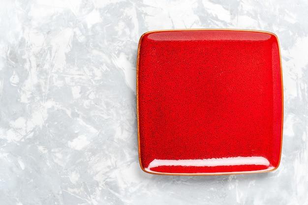 Vista superior da placa quadrada vazia vermelha ed na superfície branca