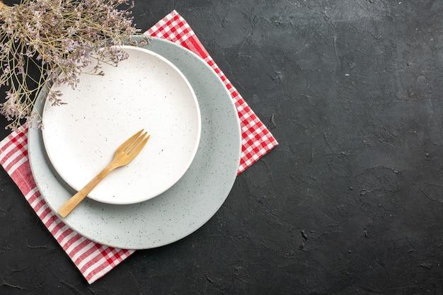 Vista superior da placa redonda branca na placa cinza no guardanapo, garfo de madeira, ramo de flores secas no espaço livre da mesa escura