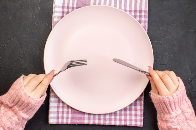 Vista superior da placa rosa com uma mulher segurando o garfo e a faca na superfície escura