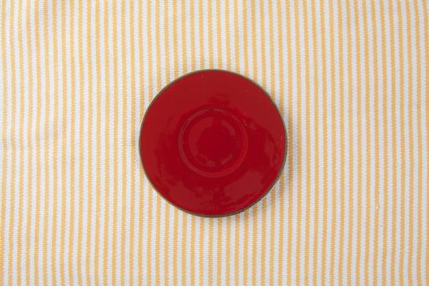 Vista superior da placa vermelha vazia colocada na mesa de pano com espaço para cópia.