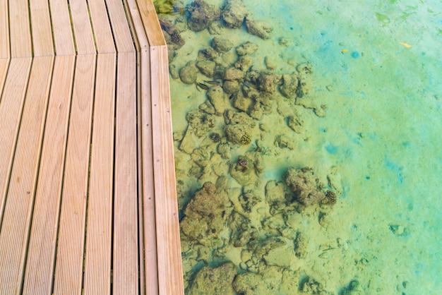 Vista superior da plataforma de madeira na ilha tropical de maldivas e na beleza do mar com os recifes de corais.