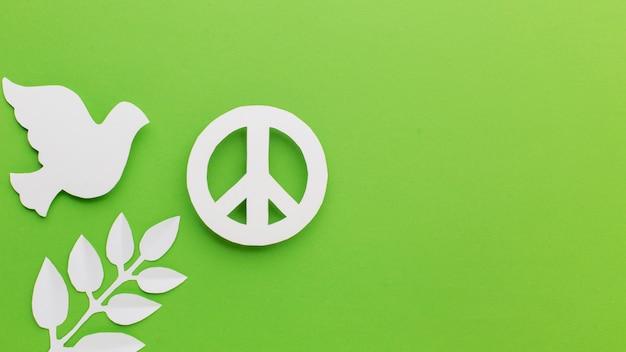 Vista superior da pomba de papel com folhas e sinal de paz