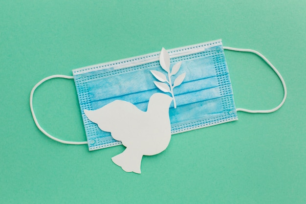 Vista superior da pomba de papel com máscara médica