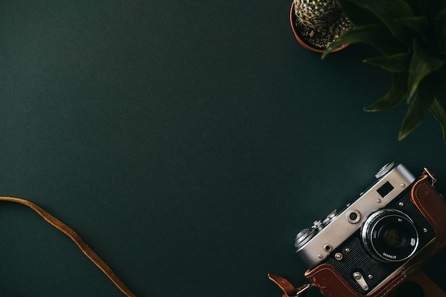 Vista superior da postura plana de uma câmera de filme sobre uma mesa vazia e escura. espaço de trabalho do conceito de um artista ou jornalista. espaço de publicidade