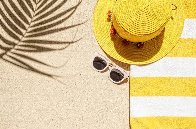 Vista superior da praia com moldura de toalha listrada de amarelo e branco e óculos de sol brancos. fundo com espaço de cópia e textura de areia visível.
