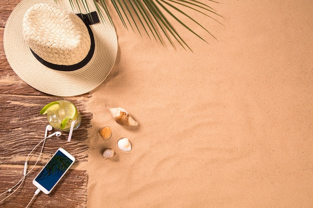 Vista superior da praia de areia com moldura de toalha e acessórios de verão. fundo com espaço da cópia e textura visível da areia. borda direita feita de toalha