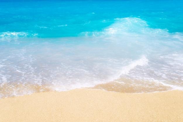 Vista superior da praia de areia com ondas e águas azul-turquesa.