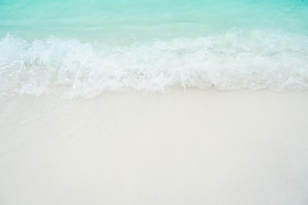 Vista superior da praia limpa da areia e da água e areia branca no verão com luz do sol - céu azul e fundo do bokeh.