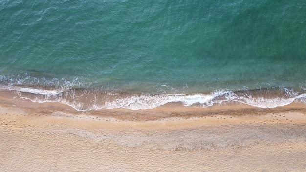 Vista superior da praia vazia e limpa e ondas do mar azul com águas claras.