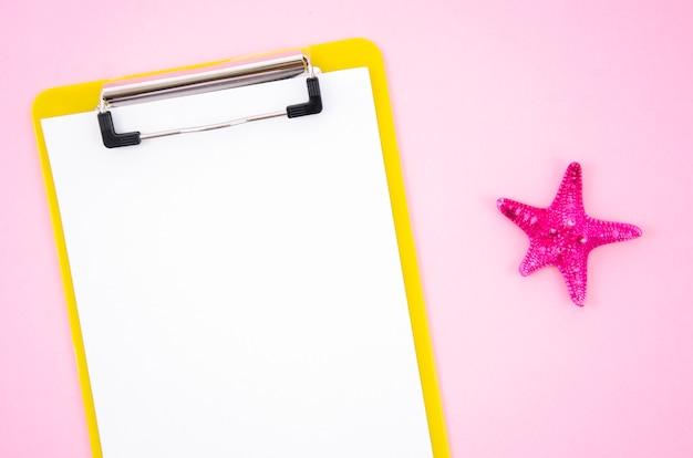 Vista superior da prancheta com um pedaço de papel em branco e estrela do mar no fundo rosa