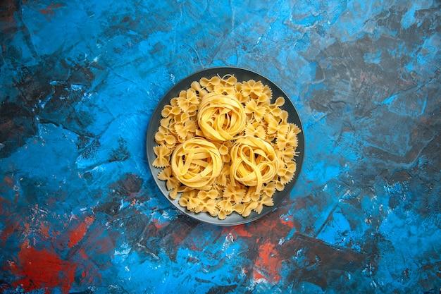 Vista superior da preparação do jantar com macarrão em uma placa preta sobre fundo azul
