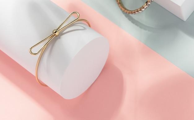 Vista superior da pulseira de forma dourada de arco no cilindro branco sobre fundo de papel de cores pastel