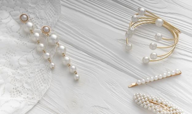 Vista superior da pulseira de ouro e brincos e alfinetes de cabelo com jóias de pérolas