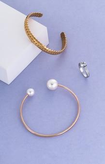 Vista superior da pulseira trançada de ouro e pulseira de ouro com pérolas e anel de noiva em ouro branco sobre fundo branco e azul