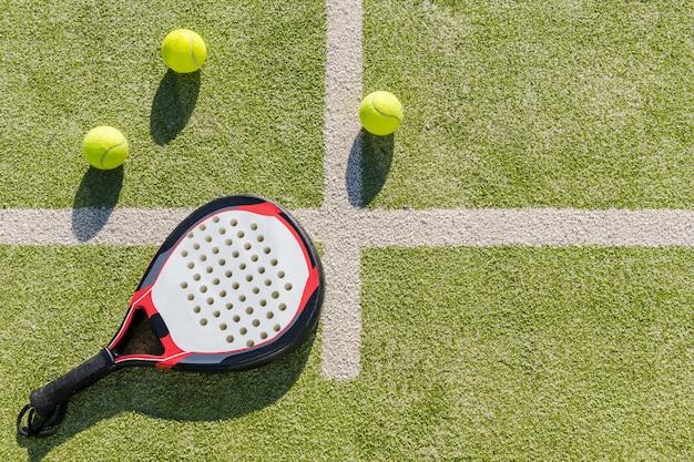 Vista superior da raquete de remo e bolas na grama