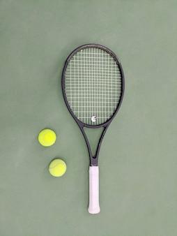 Vista superior da raquete de tênis e duas bolas na quadra de tênis de saibro verde.
