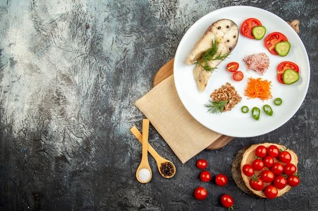 Vista superior da refeição de trigo sarraceno de peixe cozido servida com vegetais verdes em um prato branco na toalha nua na tábua de madeira e temperos na superfície do gelo
