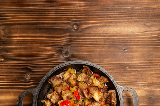 Vista superior da refeição de vegetais cozidos com carne e pimentões fatiados em uma mesa de madeira