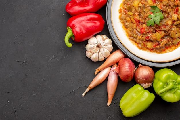 Vista superior da refeição de vegetais cozidos dentro do prato com vegetais frescos no prato de comida de refeição de fundo cinza