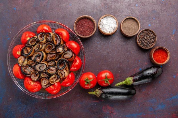Vista superior da refeição de vegetais fatiados e enrolados com tomates com berinjela e temperos na mesa escura