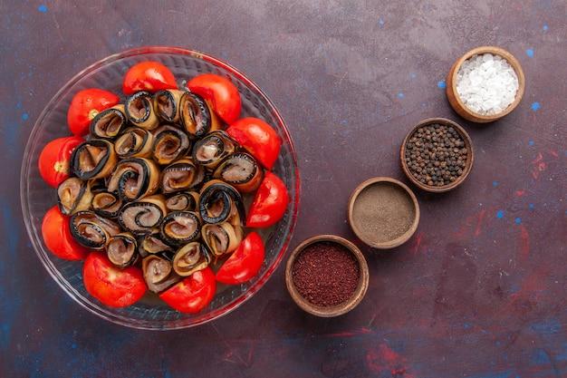 Vista superior da refeição de vegetais fatiados e laminados de tomates com berinjelas e temperos no fundo escuro