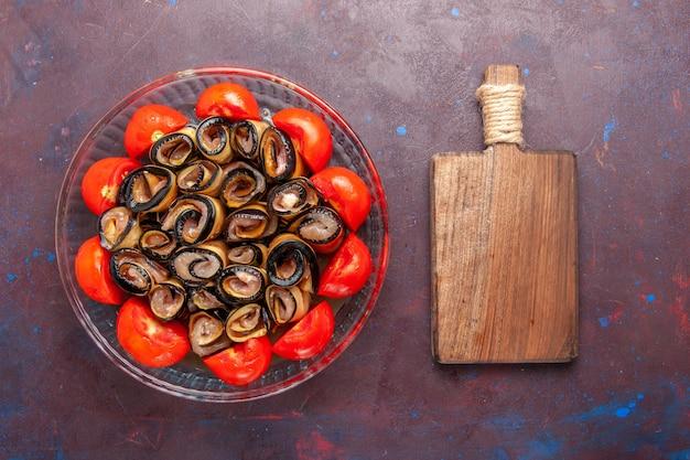 Vista superior da refeição de vegetais fatiados e laminados de tomates com berinjelas no fundo escuro